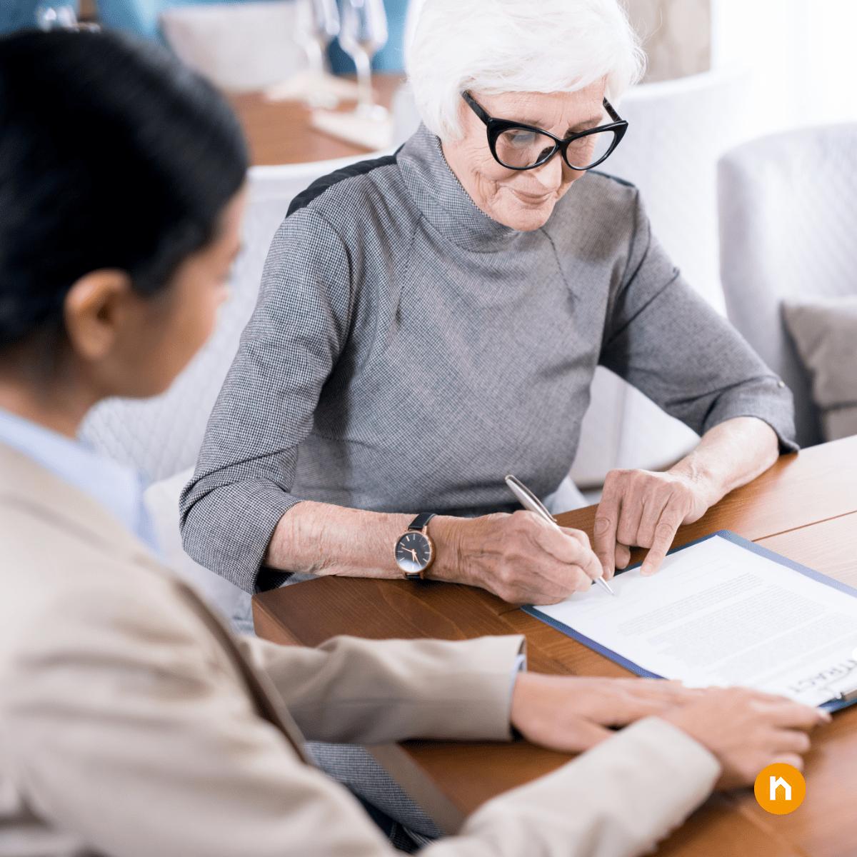Ältere Dame unterschreibt Vertrag